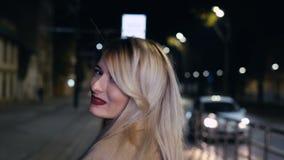 Den utomhus- ståenden av den unga kvinnan med långt blont hår, röd läppstift och stilfull blick i aftonstaden vänder till kameran stock video
