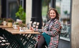 Den utomhus- ståenden av den unga kvinnan sitter i gatakafé royaltyfri foto