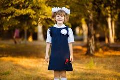Den utomhus- st?enden av den lyckliga lilla skolflickan i skolalikformig parkerar in royaltyfria foton