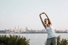 Den utomhus- sträckningen för ung kvinna arkivbild