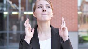 Den utomhus- unga affärskvinnan Wishing för bra lycka, finger korsade stock video