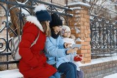 Den utomhus- vinterståenden av modern och två döttrar, familjen har gyckel i en snöstad som tar fotoet på mobiltelefonen arkivbild