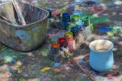 Den utomhus- workspacen av en studio för krukmakerimålningkonst med färgpaletten, borsten och den omålade krukmakerihantverkvasen arkivbilder