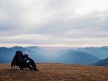 Den utpumpade turisten i svart med ryggsäcken sitter på stenen i äng och håller ögonen på in i den dimmiga dalen Höst i berg Royaltyfri Fotografi