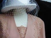 Den utsmyckade damhatten och rosa färger snör åt dräkten Fotografering för Bildbyråer