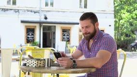 Den uttråkade sömniga mannen dricker kaffe som bläddrar smartphonen stock video
