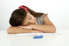 Den uttråkade studenten lägger hennes huvud på skrivbordet Royaltyfria Bilder