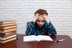 Den uttråkade, utmattade och trötta studentpojken grubblar över uppgiftssolenoiden arkivfoto