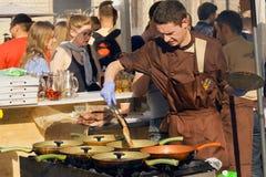 Den uttröttade kocken förbereder kötträtter i gjutjärnpannor i utomhus- kök Royaltyfri Foto