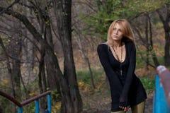 Den uttrycksfulla blondinen i kort klänning korsade hennes handc på höstbri Royaltyfri Foto