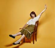 Den uttrycksfulla kvinnan sitter på stolen och 70-talblicktemat Royaltyfria Bilder