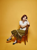 Den uttrycksfulla kvinnan sitter på stolen och 70-talblicktemat Royaltyfri Fotografi