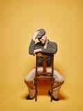 Den uttrycksfulla mannen sitter på stolen och 70-talblicktemat Arkivfoton