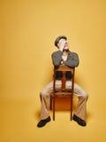 Den uttrycksfulla mannen sitter på stolen och 70-talblicktemat Royaltyfria Bilder