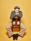 Den uttrycksfulla mannen sitter på stolen och 70-talblicktemat Arkivfoto