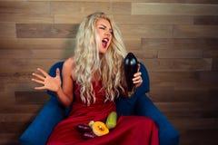 Den uttrycksfulla vegetariska kvinnan sitter på fåtöljen på bakgrund av träväggen arkivfoton