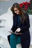 Den välklädda unga studenten skriver en rapport på hennes minnestavlaPC Fotografering för Bildbyråer