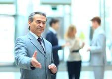Den välkomna affärsmanen ordnar till till handskakningen Arkivfoton