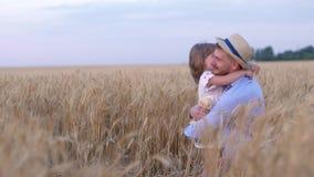 Den vänliga familjen, den lyckliga släktingfarsan och den lilla dottern har gyckel som spelar i vetefältet av moget vete under stock video