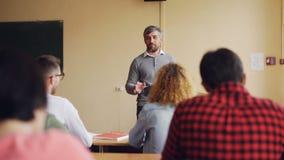 Den vänliga läraren talar till hans studenter som kontrollerar kunskap, den unga mannen, lyfter handen och den svarande frågan, a stock video