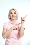 Den vänliga le mitt åldrades kvinnan som pekar på copyspace Royaltyfri Fotografi