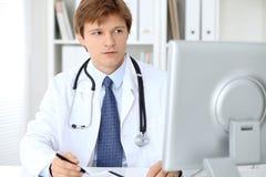 Den vänliga manliga doktorn sitter på tabellen och arbetet i sjukhuskontoret Ordna till för att undersöka och hjälpa patienter Royaltyfri Bild