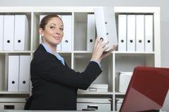 Den vänliga sekreteraren tar en mapp Royaltyfri Bild