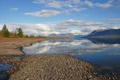 LakeLama och reflekterat i bevattnamolnen och bergen av Royaltyfri Foto