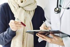Den vård- kontrollen upp, provröret för doktorsinnehavblod, läkaren och patienten diskuterar om övre rapport för vård- kontroll arkivfoto