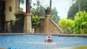 Den våta caucasian mannen får regnade enjoyes, medan simma i pöl på semester i slowmotion 1920x1080 lager videofilmer