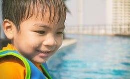 Den våta pojken sitter på poolside Royaltyfri Bild