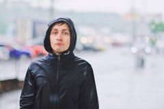 Den våta unga mannen i regnrock med den olyckliga framsidan promenerar gatan under hällregn, närbild Begrepp för stormigt väder f fotografering för bildbyråer