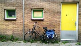 Den vanliga Amsterdam ingången i ett bostads- hus, nära en parkerad cykel Ljus gul ytterdörr arkivbild