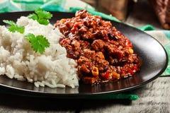 Den varma chili con carne med jordnötkött, bönor, tomater och havre tjänade som med ris Arkivfoto