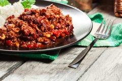 Den varma chili con carne med jordnötkött, bönor, tomater och havre tjänade som med ris Royaltyfria Foton