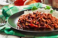 Den varma chili con carne med jordnötkött, bönor, tomater och havre tjänade som med ris Arkivbild