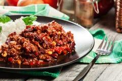 Den varma chili con carne med jordnötkött, bönor, tomater och havre tjänade som med ris Royaltyfri Bild