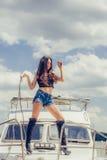 Den varma förföriska kvinnan i sexig höjdpunktsvart startar att posera på fartyget Arkivbild