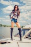 Den varma förföriska kvinnan i sexig höjdpunktsvart startar att posera på fartyget Royaltyfria Foton