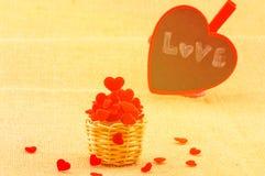 Den varma färgsignalen av hjärtor i liten trävävkorg och ett förälskelseord på en hjärta stiger ombord Arkivfoton