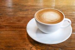 Den varma kaffecappuccinokoppen med spiral mjölkar skum på wood tabelllodisar Arkivfoton