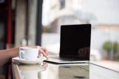 Den varma kaffekoppen nära en dator på räknarestången illustrerar rel Arkivfoton