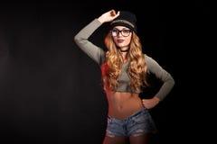 Den varma sexiga kvinnan med jeans kortsluter på svart bakgrund Fotografering för Bildbyråer