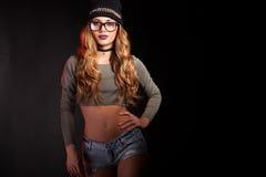 Den varma sexiga kvinnan med jeans kortsluter på svart bakgrund Arkivbild