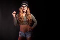 Den varma sexiga kvinnan med jeans kortsluter på svart bakgrund Royaltyfri Bild