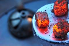 Den varma vattenpipan bränner till kol, Litkol för vattenpipa, vattenpipategelplatta, värme, brand, varma kol, bunke med tobak oc arkivfoton