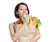Den vegetariska flickan äter ett äpple royaltyfri foto