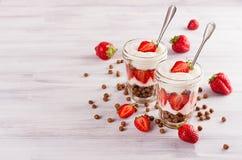 Den vegetariska frukosten med choklad klumpa ihop sig havreflingor, skivad jordgubbe på det vita wood brädet Dekorativ gräns med  Royaltyfri Bild