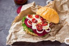 Den Vegitarian hamburgaren med betaskivor, microgreen groddar, tofuost, torkade tomater och löken på kraft packepapper på den mör Arkivfoto