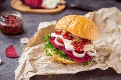 Den Vegitarian hamburgaren med betaskivor, microgreen groddar, tofuost, torkade tomater och löken på kraft packepapper på den mör Fotografering för Bildbyråer